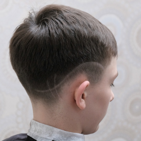 Fashionable haircut with a shaved pattern on the head of a teenager. The result of the work of a hairdresser in a beauty salon. A square picture. Banque d'images