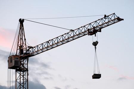 Budowa żurawia wieżowego z obciążeniem na tle wieczornego nieba