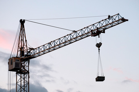 Construction tower crane with a load against the background of the evening sky