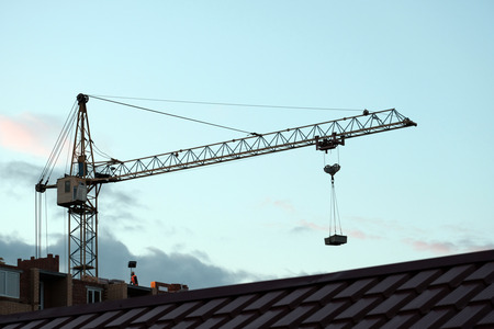 Home construction. Tiled roof in the foreground. Arrow of a tower crane with a load against the background of the evening sky.