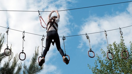 A girl in black jeans and a white T-shirt passes an obstacle course above the trees against the sky with clouds. Summer rest. Extreme entertainment. Stock Photo
