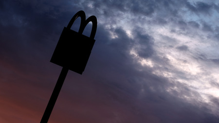Kostanay, Kazakhstan, July, 2018. Symbol of a round-the-clock power point. The McDonalds logo on the top of the post on the background of sunrise or sunset. Editorial