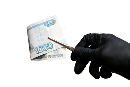 A close-up of a man's hand in a black glove that holds one thousand Russian rubles with tweezers. The concept of paid medicine and corruption, violation of the law and the work of a criminalist or a scientific laboratory assistant. Copy space. Isolated on white background.