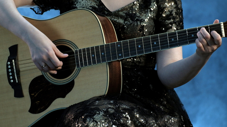 Woman play on the acoustic guitar. The fingers of the left hand of the beautiful girl clamp on the strings a chord in E minor.