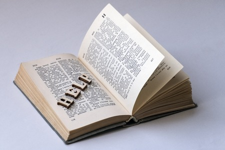 English-Russian dictionary. The word HELP from wooden letters is laid out on the page of the book. The concept of self-learning a foreign language, preparing students for exams. White background. Stockfoto