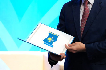 The concept of awarding a civil servant. A man in a dark suit holds a opened folder with the image of the national flag of the Republic of Kazakhstan. Blue background. Copy space.