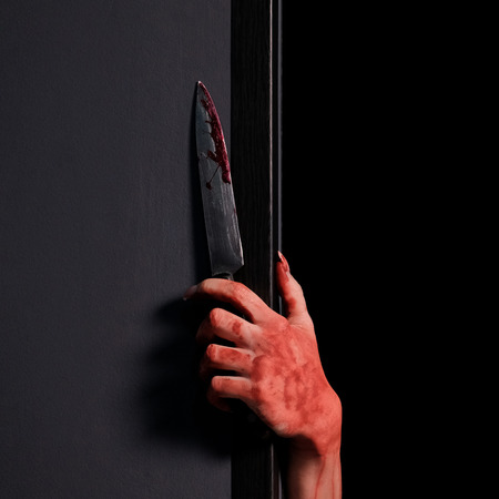 Female hand looks out from behind the wall with a bloody knife.Halloween celebration concept. Close-up. Square picture frame. Black background.