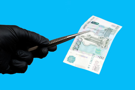 A man holds money in medical gloves. On the isolate blue blackground.