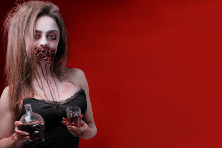 A woman with Halloween make-up is holding a carafe and a skull glass in her hands. Festive party. The face of a girl with a mouth sewn up and bloody smudges on the neck and arms. Red background. Copy space. Фото со стока