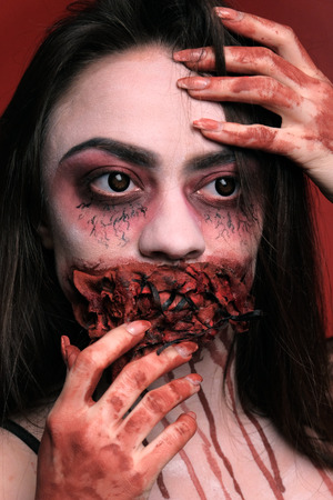 Scary makeup for halloween. Blood on the hands. Vertical portrait of a girl with a mouth sewn up and bloody smudges around her neck on a red background. Close-up.