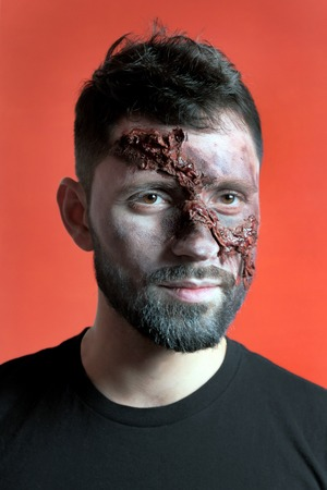 Vertical portrait of a young man with ragged facial wounds. The guy in the black t-shirt with makeup in the style of Halloween. Festive party. Red background.