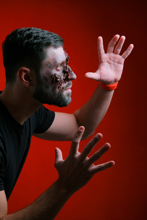 The guy in profile with Halloween-style makeup raised his hands and spread his fingers. Close-up. A young man with a torn wound and bruises on his face. Dark red background. Stock Photo