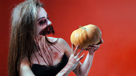 Makeup concept for horror story. The girl in the style of Halloween is holding an orange pumpkin. Imitation of a bloody wound and a wired mouth on a woman's face. Red background. Copy space. Gothic party theme. Standard-Bild