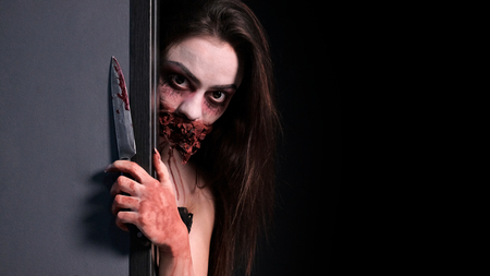 Makeup for halloween party. Imitation of a bloody wound and a wired mouth. A girl with a bloodied knife in her hand looks out from behind a gray wall. Black background. Copy space. Horror story concept.