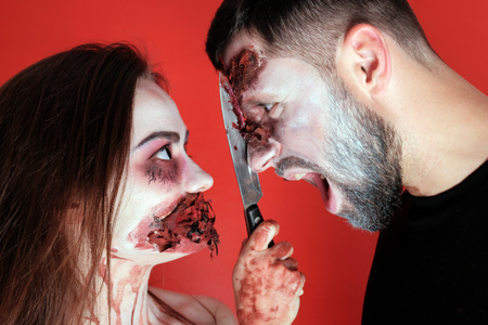 Halloween concept of makeup for All Saints or the Dead. The guy screams at the time when the girl cuts his face with a bloody knife. Horrible cosplay. Close-up. Torn wounds on the face and darned mouth.