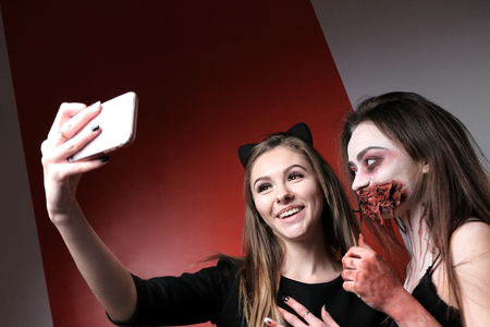 Two girls with long hair laugh while taking a selfie. Photographing terrible makeup on the phone in the style of Halloween. Preparing for a party in a dark gothic theme. Red and white background. Copy space.
