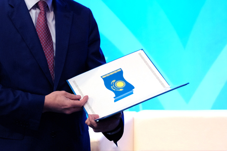 The concept of awarding a civil servant. A man in a blue suit holds an open folder with the image of the national flag of the Republic of Kazakhstan. Copy space. Stockfoto