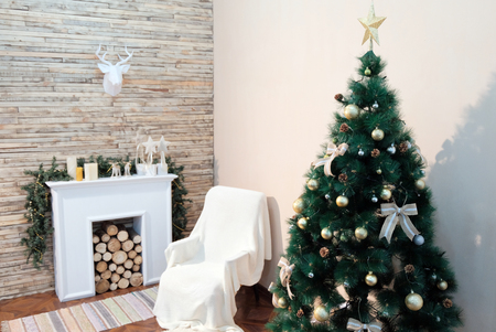 Christmas tree stands near the bedside table and fireplace against the white wall. Paper deer head hanging on the wall of wooden planks. Theme happy new year.