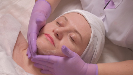 Middle-aged woman on the procedure in the cosmetology center. Close-up. The hands of a cosmetologist in lilac gloves put a soap solution on the female face. Stock Photo
