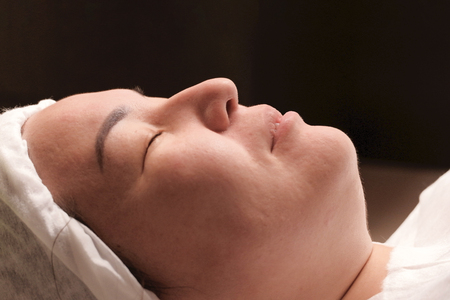 Eastern woman lies on the procedure of skin rejuvenation in the beauty salon of a medical center. Skin rejuvenation and scrubbing. Close-up.