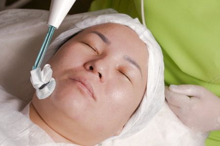 Close-up of the face of a Muslim woman on the physiotherapy facial rejuvenation procedure. Darsonvalization. Activation of blood circulation, improvement of tissue nutrition, elimination of acne.