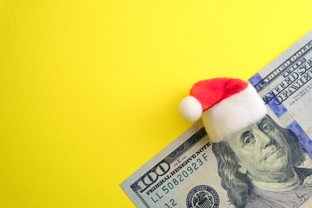 Red Santa hat on Franklin's head on one hundred dollars. Yellow background with copy space.