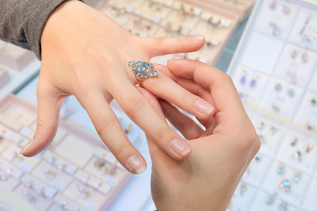 A girl in a jewelry store tries on her finger a gold ring with diamonds on the background of a shop window. Woman jeweler. Buying and shopping.