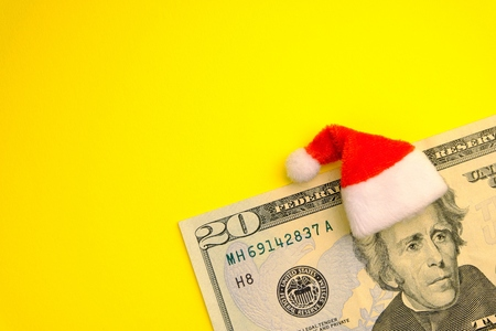 The concept of the cost of Christmas holidays, debt, profits or discounts for the new year. President Jackson wearing a red Santa Claus hat on a twenty-dollar US bill on a bright yellow background. Copy space.