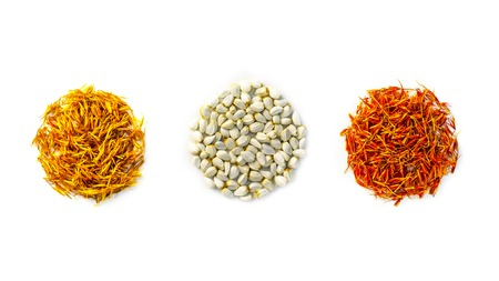 Yellow, red dried safflower petals and seeds Carthamus tinctorius are folded in the form of circles on a white background. Isolated Copy space.