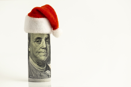 President Franklin as Santa Claus. Humorous concept. The hundred-dollar bill is hung up with a red cap at the top of its head. New Year or Christmas financial surprise. White background. Copy space. Banco de Imagens