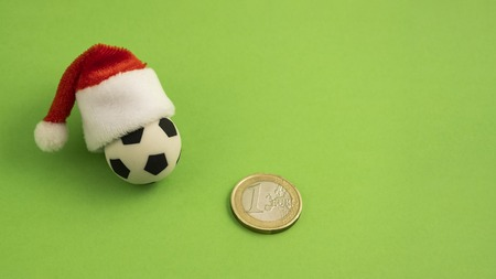 A souvenir soccer ball in a red Santa Claus hat next to a one euro coin on a green background. Concept sports betting or a Christmas present. The symbol of football victory in the new year. Copy space. Stock Photo