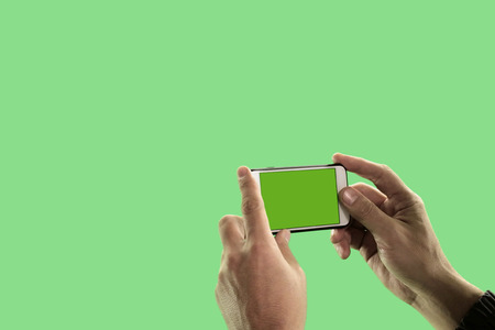 The guy takes pictures or shoots video on a mobile phone. Close-up of the hands of a man with a gadget on a green background. Chroma Key. Фото со стока