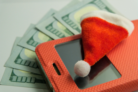 Souvenir Santa Claus hat lying on a smartphone in a red case against the background of five hundred US dollars. Close-up. The concept of New Years recharge mobile phone or a gift for Christmas.