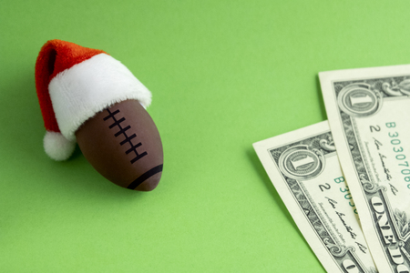 A souvenir american football ball in a red Santa Claus hat next to two one-dollar bills on a green background. The concept of Christmas sports betting or corruption and financial fraud on the New Year Stock Photo