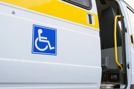 White bus with a blue sign for the disabled. The open door of a specialized vehicle for people with disabilities. Yellow bar and handrail.