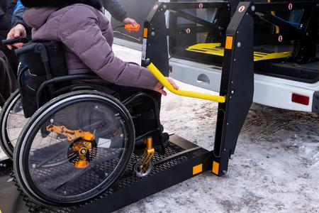 Un uomo preme un pulsante sul pannello di controllo per far salire una donna su una sedia a rotelle in un taxi per disabili. Veicolo specializzato Black lift per persone con disabilità. Corrimano giallo. Orario invernale.