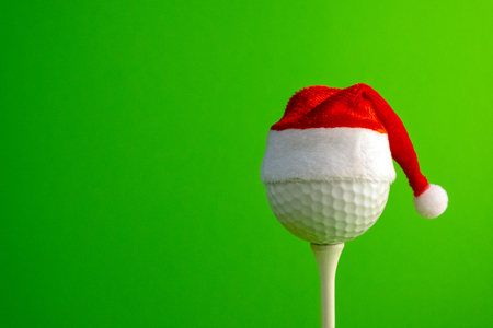 Golf ball in a red Santa Claus hat mounted on a tee. Sports concept on the theme of Christmas and New Year. Copy space. Green background.