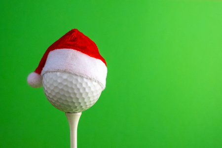 Sports concept on the topic of golf, Christmas and New Year. White golf-ball in a red Santa Claus hat set on a tee. Green background. Copy space.