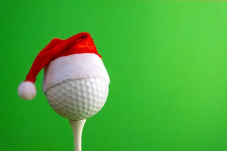 Golf ball on a tee with a red santa claus hat. Template for design greeting card for golfer for new year or christmas. Green background. Copy space.