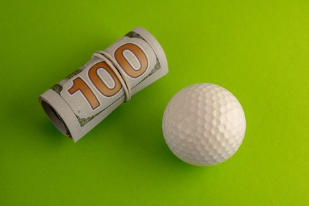 A stack of one hundred US dollar bills rolled into a roll and tied with a rubber band is next to a golf ball against a green background. The concept of sports betting, golfing competitions for money.