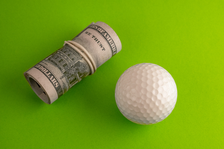 Golf ball next to a roll of hundred dollar bills of the USA with a white rubber band. The concept of sports betting or competition for money, financial risk or corruption. Green background. Stock Photo