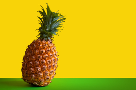Beautiful ripe pineapple on a green table against the background of a yellow wall. Template for packaging or advertising of exotic fruit or juice. Copy space. Clipart for the designer. Standard-Bild - 114940458