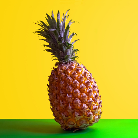 Square frame for pineapple advertising. Ripe sweet exotic fruit stands on a green table with a yellow background. Copy space. Clipart for bright design. Foto de archivo - 114940460