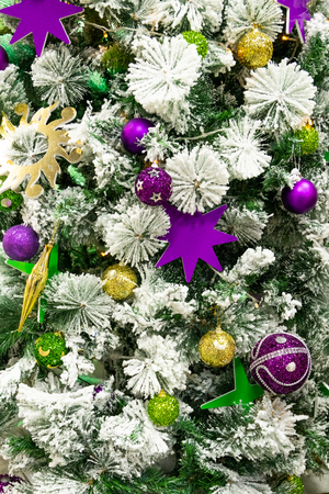 Bright abstract background for the design of the New Year and Xmas holidays. Golden and lilac balls and stars on the Christmas tree.