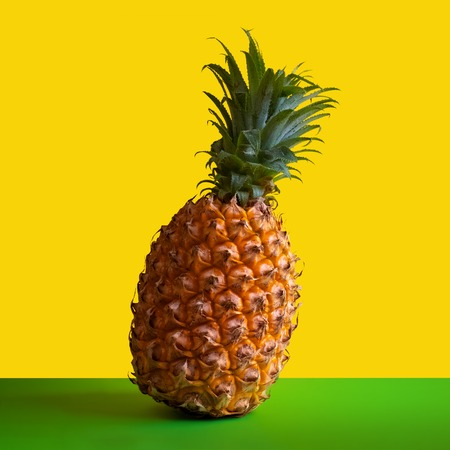 Ripe pineapple on a square frame. Concept of advertising of tropical fruits or picture for instagram. Yellow background. Copy space. Foto de archivo - 114939860