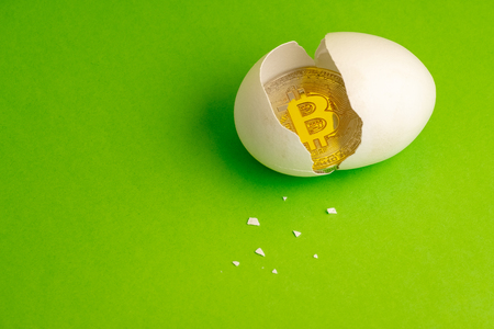 Gold Bitcoin coin in a broken egg. White eggshell with cryptocurrency symbol inside instead of yolk. Bit-coin birthday concept. Green background. Copy space.
