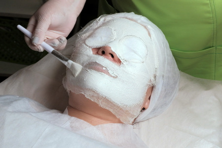 Woman in beauty salon with white mask on her face. A cosmetologist s or physician s hand applies a plaster solution to the patient s face with a brush. The procedure of rejuvenation and cleansing.