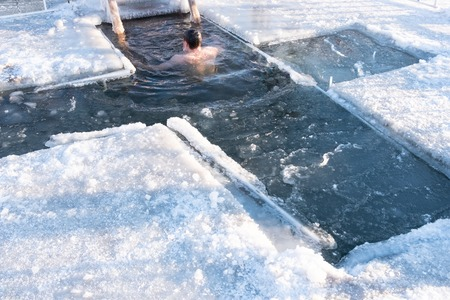 Holidays of Orthodox baptism.A man is immersed in ice water. Ice hole on the river in the ice in the form of a cross.