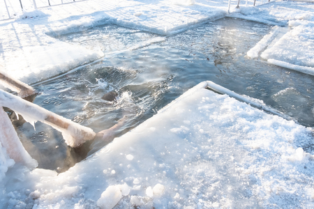 The man plunged headlong into cold water into a hole-cross on the river. Holidays of Orthodox baptism. Wooden railing covered with ice. Winter tradition.