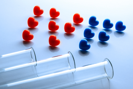 Concept of in vitro fertilization. The third attempt. Abriveatura IVF from red and blue hearts and three test tubes in the foreground. The theme of the dream of a newborn. Copy space.